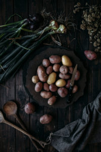 Red potatoes and onions on dark wooden background
